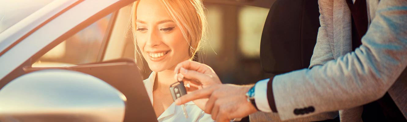 Young woman getting keys for new car
